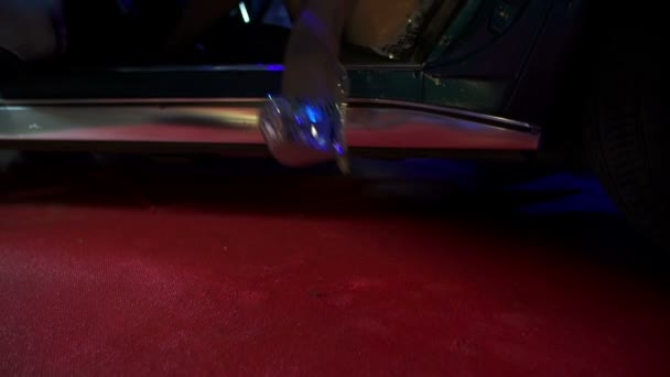 Some woman stepping out of a Corvette at night