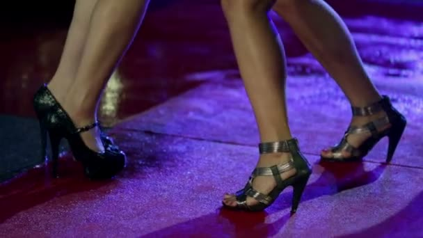 Women legs making dancing moves on wet red carpet
