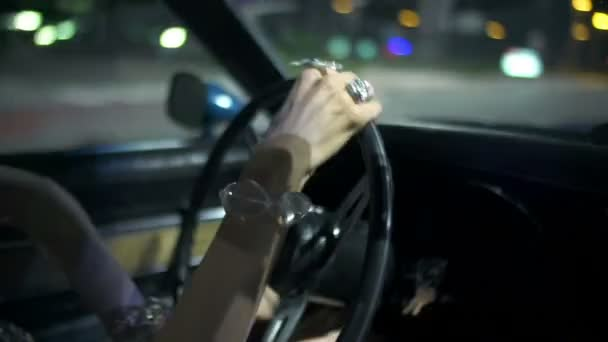 Woman driving Corvette with glittering jewellery on her hands
