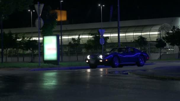 Blue car drives past the camera screen at night