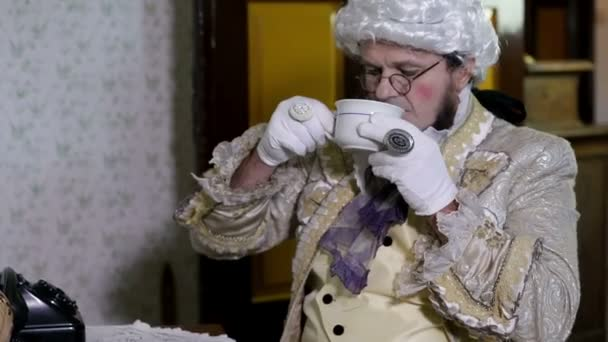 Man with a white wig is drinking a cup of tea