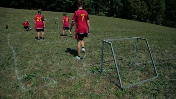 děti hrají s míčem na fotbalové hřiště