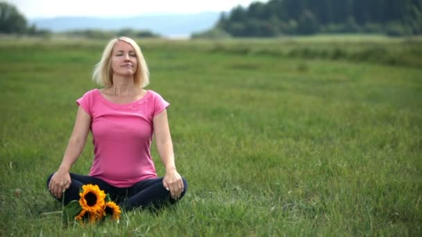 žena v lotosové pozici zhluboka nadechuje a zavře oči