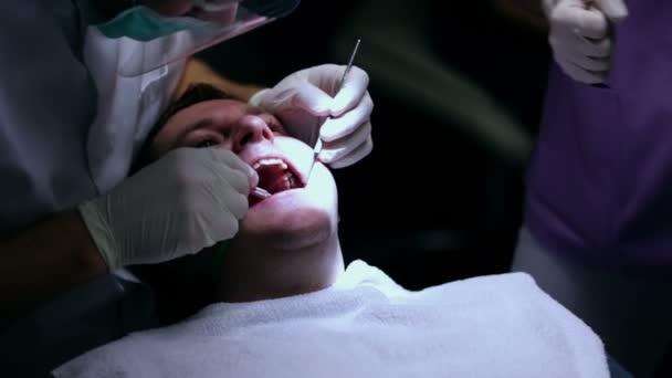 Dentista lavora con il cliente che si guarda intorno