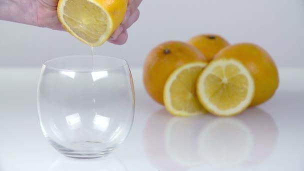 mačkání citrónovou šťávu do průhledného skla