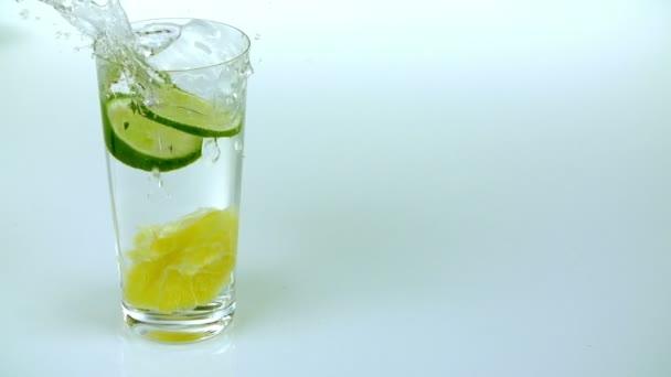 dva kusy vápna spadají do sklenici vody s citronem