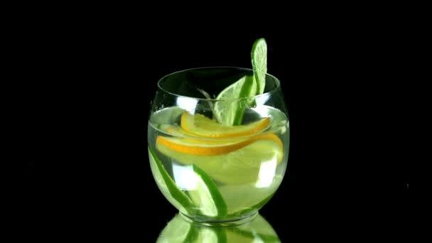 kousky citrusů spadají do sklenice vody s limetkou a plátky citronu