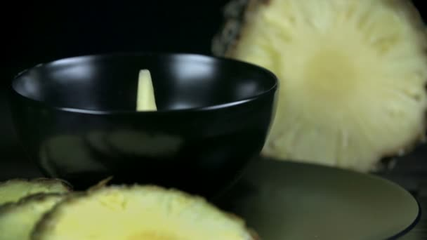 Pieces of pineapple falling into black cup in slow motion