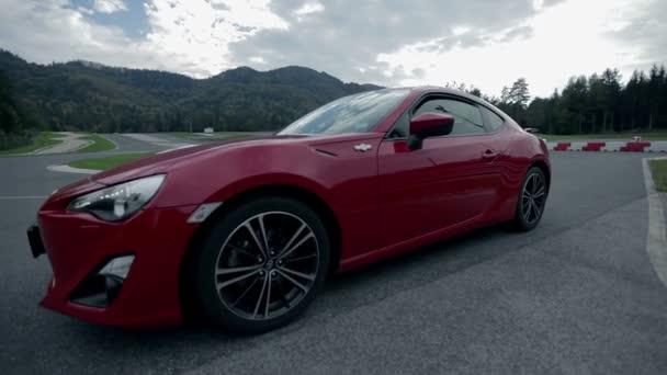 červené sportovní auto odežene na závodní dráze.