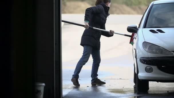 žena mytí auta s koštětem v pomalém pohybu