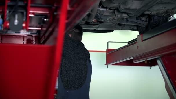 automechanik, pracující pod auto