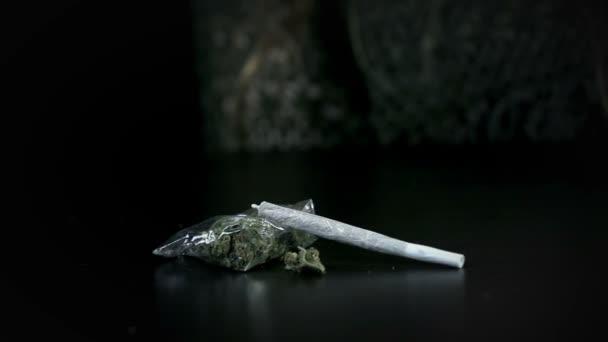společné padá na balíček marihuany na černém pozadí v slo-mo