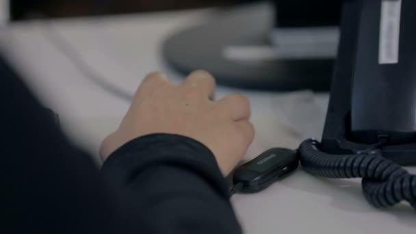 Helpdesk operátor přijímá volání po telefonu na jejím stole