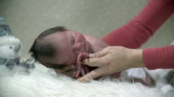Mother lays her baby on a soft furry blanket