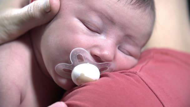 Detail of baby with pacifier in his mouth