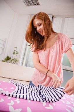 Woman Folding Clothes On Ironing Board