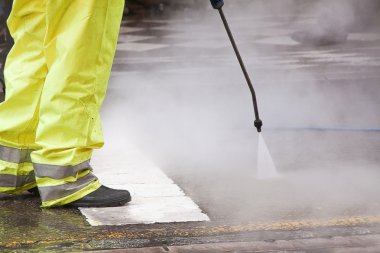 A worker cleaning the streets with water pressure