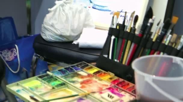 Künstler-Malerei-Bild mithilfe der Palette und verschiedenen Pinseln