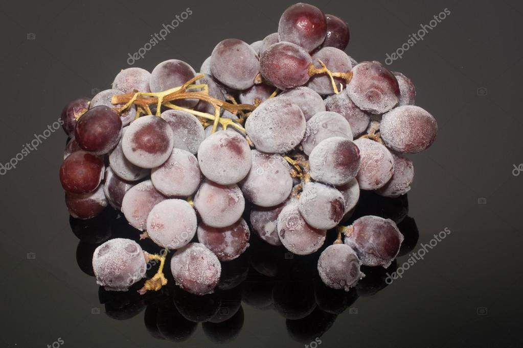Frozen grapes or Grapes in ice Isolation on the black background