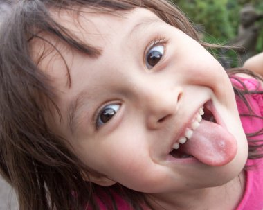 Young girl sticking out tongue while making funny face
