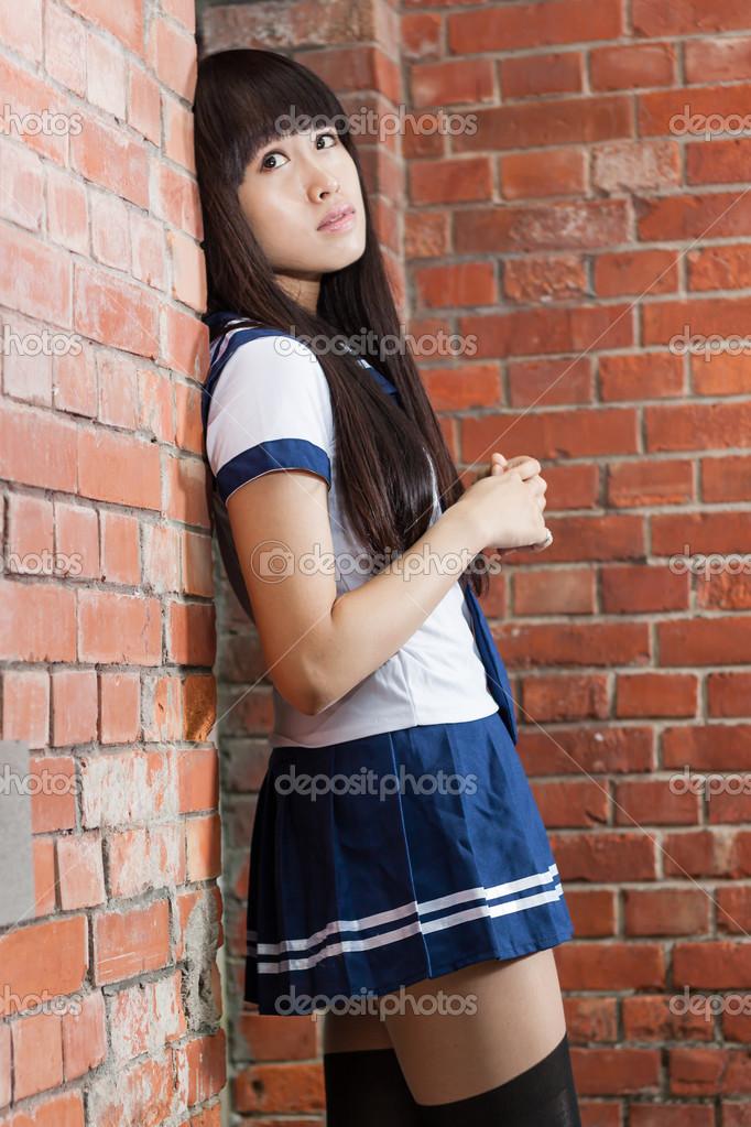 Asian Schoolgirl Outside Brick Building Stock Photo