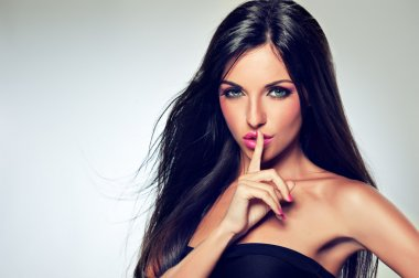 Brunette woman showing silence gesture