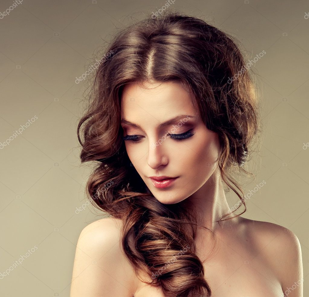 bella mujer morena con pelo largo y rizado mirando hacia abajo u foto de