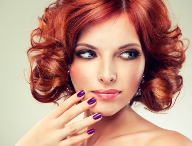 Redhead woman with bright makeup and manicure looking to the left