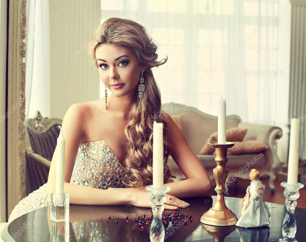 Красивая девушка сидит за столом