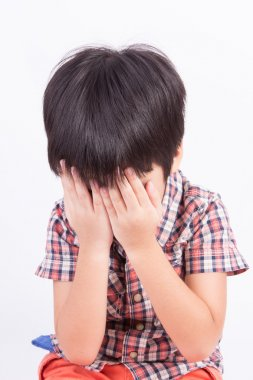 Young little boy crying or playing with hiding face