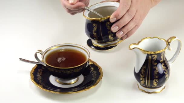 Lady adding brown sugar to cup of beautiful china tea set