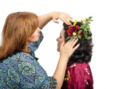 Red-haired hairstylist putting in a red rose in her hair custome