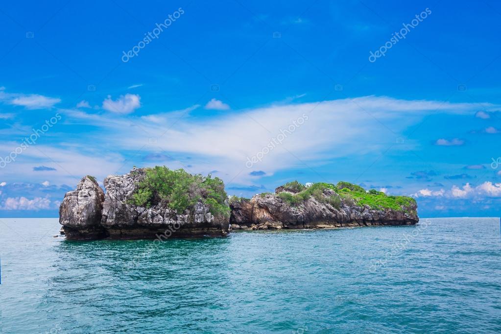 Tropical rock island against blue sky and  sea