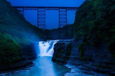 Upper Falls and a train bridge during twilight, at Letchworth St