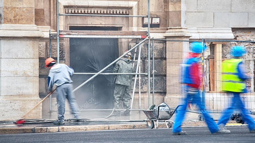 Construction workers cleaning a building