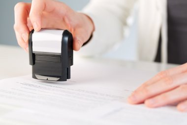 Person placing a stamp on a document