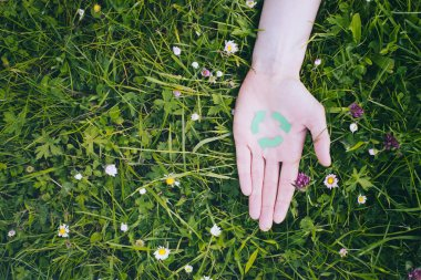 Hand with Recycle Symbol on Grass