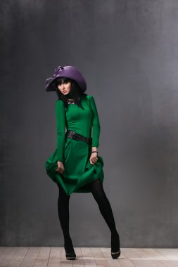Beautiful sexy woman in a green dress and purple hat