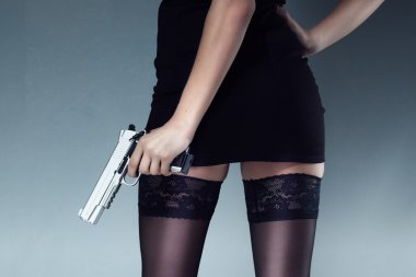 Sexy brunette girl in a black dress boots holding a gun and looking back