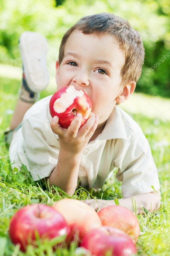 Boy eating a red apple