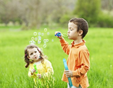 Children blowing bubbles outdoors.Focus on the boy stock vector
