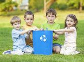Fényképek Childdren a füvön az újrahasznosítási szimbólum