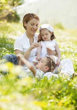 Happy family sitting on flowers field