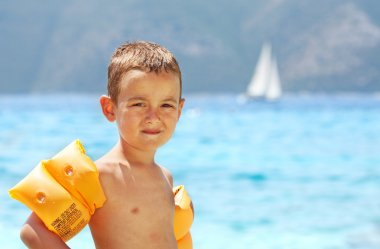 Little boy standing near sea wearing orange inflatable armbands
