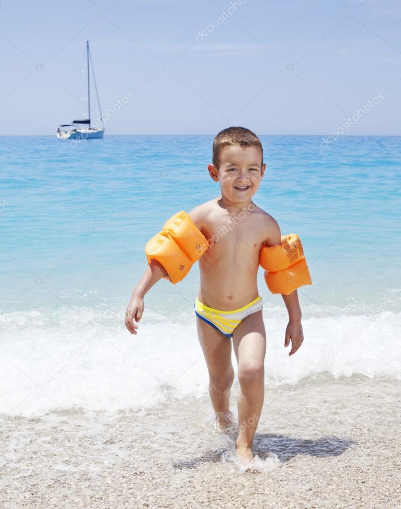 Little boy running on a beach wearing orange inflatable armbands