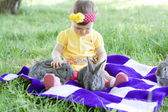 Cute baby with bunnies outdoors
