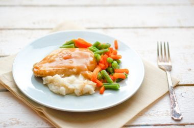 Oven baked chicken in gravy with mashed potatoes and vegetables