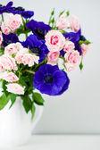 bouquet di rose rosa e blu anemoni in vaso bianco