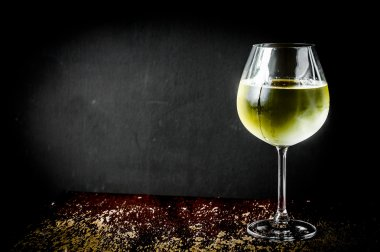 Glass of chilled white wine on wooden background