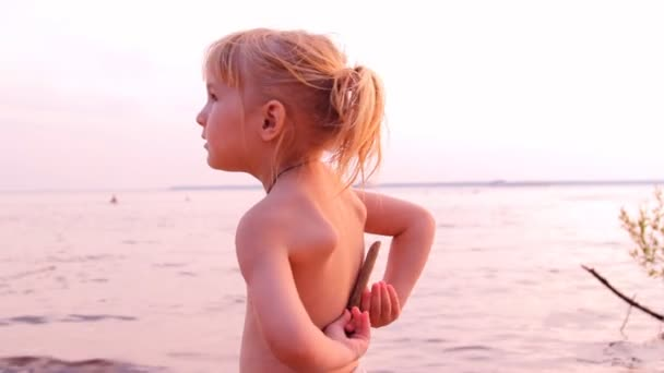 Little girl plays, looks afar at water